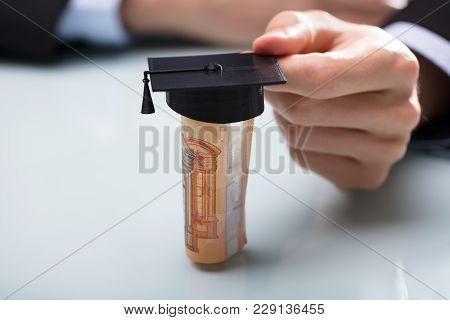 Close-up Of A Human Hand Placing Graduation Hat Over Rolled Up Banknotes On Desk