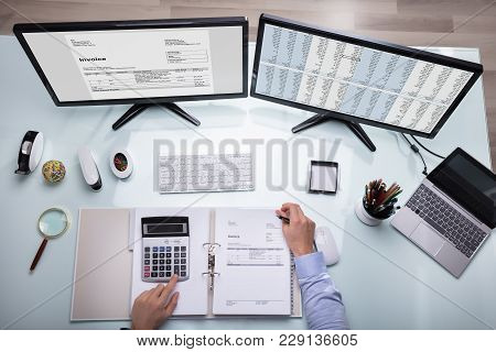 Businessperson Calculating Invoice With Calculator