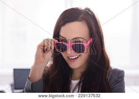 Portrait Of A Young Businesswoman Wearing Pink Sunglasses In Office