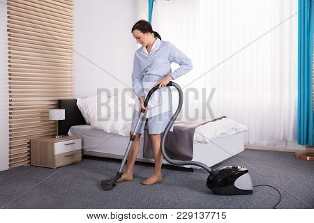 Happy Young Housekeeper Cleaning Carpet With Vacuum Cleaner In Hotel Room