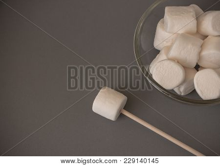 The marshmallows in a clear bowl on the gray background. The white sugar-based candy, sweet, soft, chewy confection made with sugar and gelatin. poster