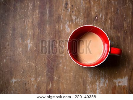 Hot Chocolate Milk In The Red Mug On The Wooden Table. The Sweetened Beverage Made By Blending Milk