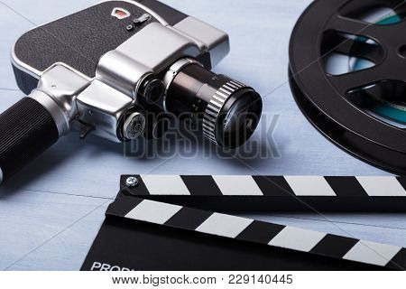 Close-up Of Movie Camera With Film Reel And Clapper Board On Wooden Desk