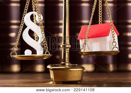 Close-up Of Paragraph Symbol And House Model On Golden Justice Scale