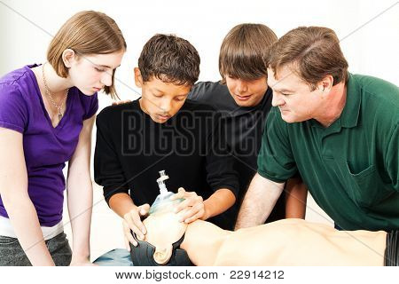 Teenage students and their teacher, using an oxygen mask on a CPR dummy.