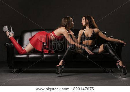 Two Sexy Women In Bdsm Style Red And Black Leather Wear Relaxing On A Sofa Shot
