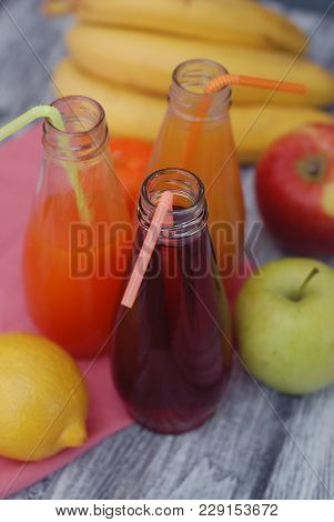Juice Glasses Of Freshly Fruit Juice With Colorful Fruits On Rustic Gray Wooden Background.