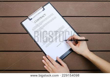Beautiful Flat Lay Of Young Woman Hands With Pen Sign Contract, Wooden Backgroung. Concept Of Busine