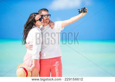 Happy Couple Taking A Photo On White Beach On Honeymoon Holiday