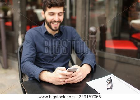 Gladden Male Person Sitting At Cafe Table And Chatting With Wife By Smartphone With Close Up Face In