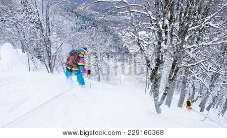 Two Skiers In Bright Suits Descend Down The Steep Mountain, Freeride In The Mountains, 4k.