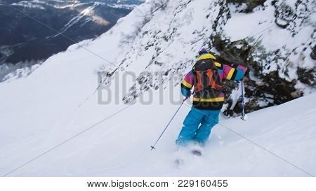 A Skier In A Bright Suit Goes Down From A Steep Mountain, Freeride In The Mountains, Slow Motion.