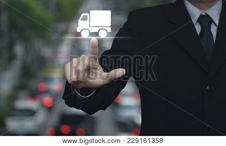 Businessman Pressing Truck Delivery Icon Over Blur Of Rush Hour With Cars And Road, Business Transpo