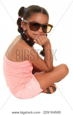 Small multiracial girl  with sunglasses sitting on the floor - Isolated on white