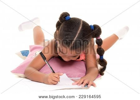 Small multiracial girl laying on the floor writing - Isolated on white