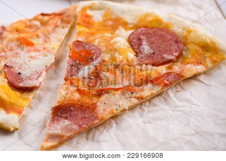 Slice Of Hot Classic Pepperoni Pizza On Baking Paper, Close Up. Fresh Pizza With Pepperoni, Mozzarel