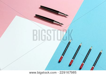 White Sheet Of Paper, Black Pencils And A Pens On A Blue And Pink Surface. Creative Concept