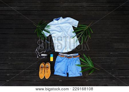 Man Summer Clothes Collage Flat Lay Isolated On Dark Wood Background. Summer Outfit Of Casual Man De
