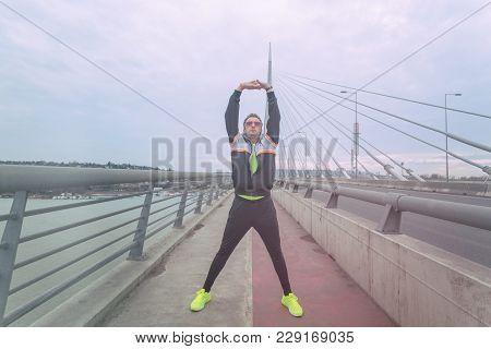 Urban Jogger Stretching On A Big Bridge.