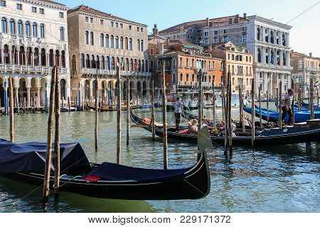 Venice, Italy - August 13, 2016: Tourists In Gondola At The Pier Of Grand Canal