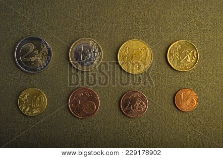 Coins Of Euro And Euro Cents On A Background Of A Dark Golden Background. Closeup. Currency Of The E