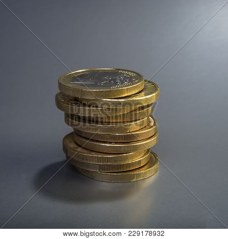 Pile Of Coins Is One Euro On A Dark Gray Background. Closeup. Currency Of The Euro