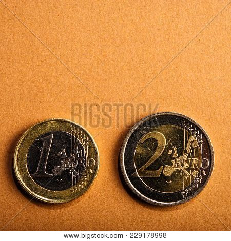 Coins One And Two Euros On A Background Of Cardboard. Closeup. Currency Of The Euro Union.