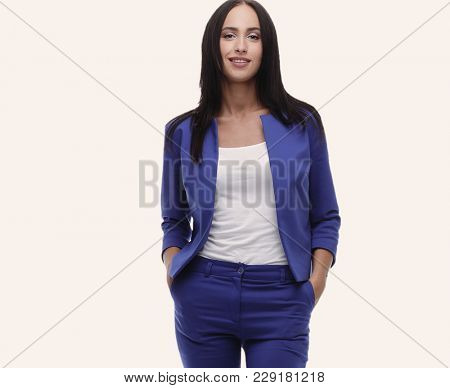 Confident young businesswoman standing with hands in pocket, loo