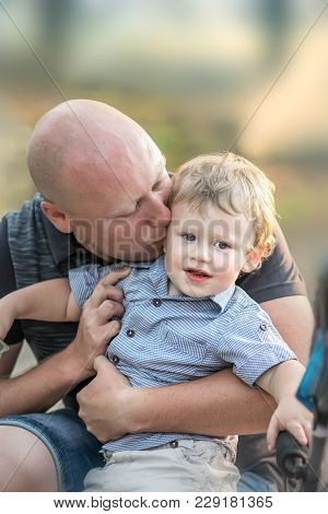 A Happy Baby Boy And A Kissing Him Young Father At Summer Park. A Loving Father Hugging And Kissing