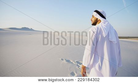 Charming Young Male Arab Looks Toward Sun And Goes Up Sand, Examining Landscapes Of Wide Desert. Mus
