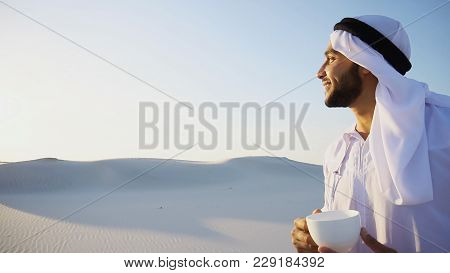 Handsome Male Arab Tastes Coffee Drink From White Cup And Enjoys Peaceful Morning, Smiling And Stand