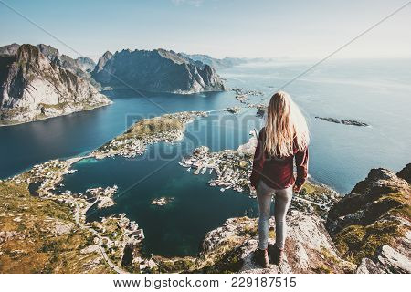 Tourist Woman Standing On Cliff Of Reinebringen Mountain Aerial View In Lofoten Islands Of Norway Tr
