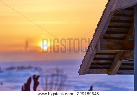 Romantic Winter Holiday On The Shore Of A Large Lake. Beautiful Winter Sunset. A Hotel Complex In Th