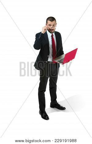 Handsome Young Bearded Man Standing At White Studio Background With Laptop. Full Body Portrait Of Bu