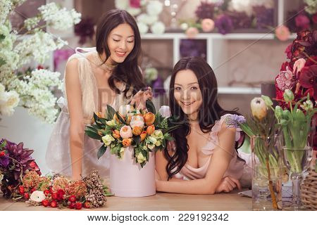 Beautiful Asian Florist Girls Making Bouquet Of Flowers On Table For Sale Against Floral Bokeh Backg