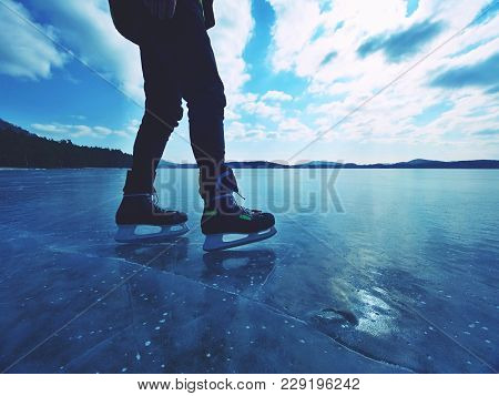 Long Male Legs In Black Leggins With Hockey Skates. Outdoor Ice Skating On The Lake