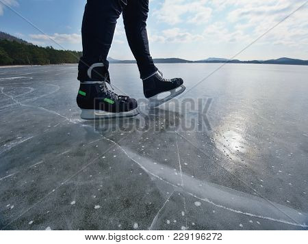 Man Ice Skating On Frozen Lake. Thin Ice With Deeep Cracks Below Man Legs.