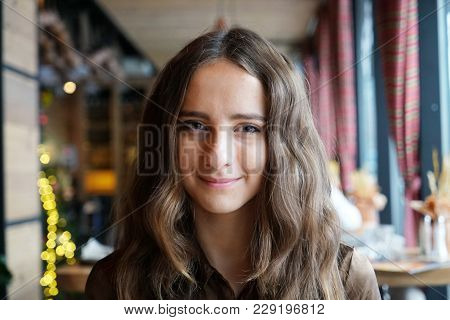 Cute Smiling Girl Sitting In A Cafe. She Has Big Brown Romantic Eyes. With Nice Brown Long Hair. Wea