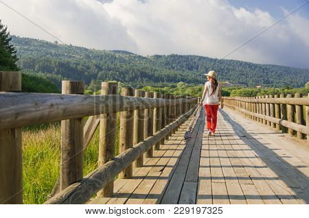 Young Woman Walking On The Wooden Path Along The Lake Shore. There Is A Red Pantone, A White Shirt A