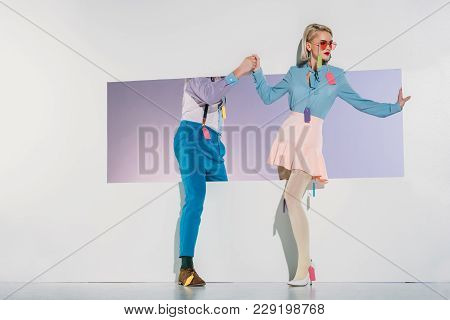 Attractive Couple In Fashionable Clothes With Sale Tags Holding Hands On White