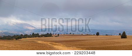 The Beautiful Summer View Of The Plowed Field And Mountains In Are Far At A Partly Cloudy.