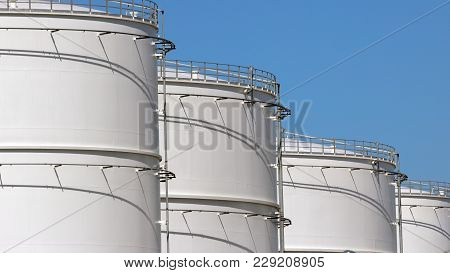 Row Of Large White Oil Storage Tanks.