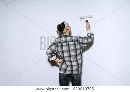 Young Girl In Plaid Shirt Colors The Wall With A Platen In White Color
