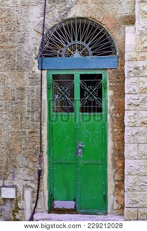 Green Door In An Old Building With Blue Arch On Top