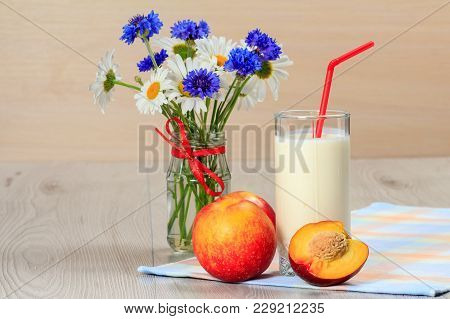 Glass Of Delicious Yogurt With Mint And Fresh Nectarine, Chamomile And Cornflowers In Vase On Wooden