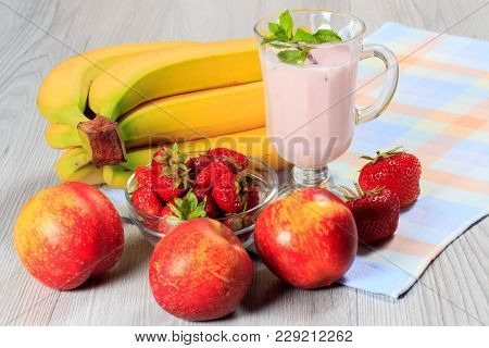 Glass Of Delicious Yogurt With Mint And Fresh Strawberries, Banana, Nectarine On Wooden Table With N