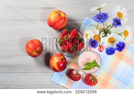 Strawberry Yogurt In Glass With Fresh Strawberries, Nectarine, Chamomile, Cornflowers On Wooden Tabl