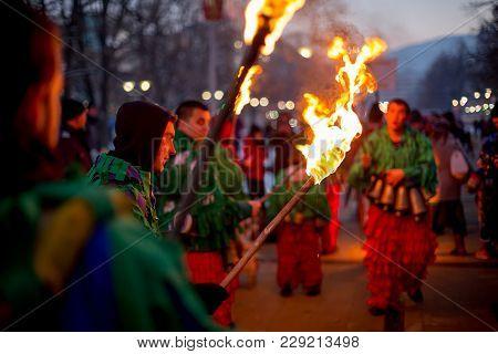 Pernik, Bulgaria - January 26, 2018: Young Man, Part Of Big Kukeri Group Holds Burning Torch And Loo