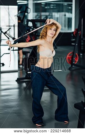 Woman In The Gym With Red Hair Shows Her Weight Loss. She Measures The Coverage Of The Waist And Che