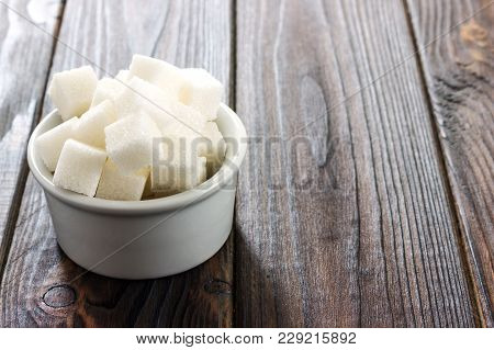 Sugar Cubes In Ceramic Bowl On Wooden Table.